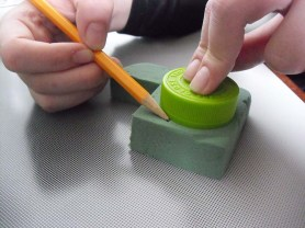 PHOTO: hands tracing around a bottlecap and block of foam with a pencil.
