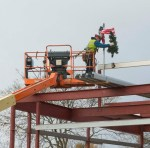 """PHOTO: A construction worker """"tops off"""" the site, as the team reaches the halfway point in the construction of the new campus."""