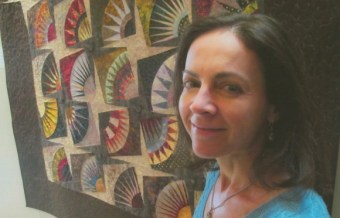"PHOTO: Amy Spungen with her quilt, ""Fanfare"""