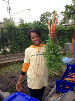 PHOTO: Juaquita holds up a freshly washed carrot harvest.