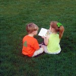 PHOTO: A girl reads a book to her friend on the lawn in summer.