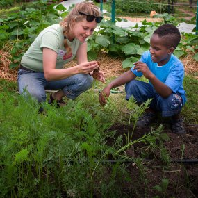 PHOTO: A young boy learns some urban agriculture skills with Windy City Harvest.