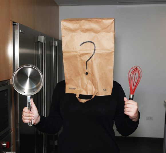 A girl with a bag over her head, holding a pot in her right hand, a whisk in her left.