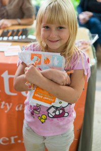 PHOTO: A smiling girl holds her completed Garden Bingo sheet and a fistful of candy.