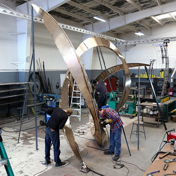 Photo: Studio staff assist in welding a larger piece.