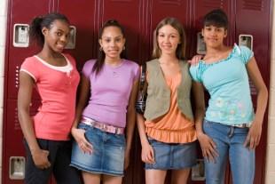 Smiling teenage girls standing by lockers
