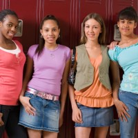 Smiling teenage girls standing by lockers