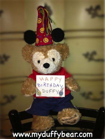 Duffy the Disney Bear holds up Happy Birthday sign