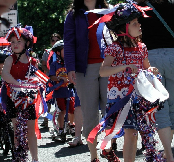 The children's parade is a sea of red, white and blue on bikes, scooters, wagons and strollers.