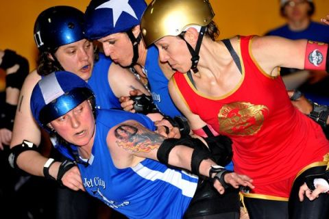 Elaine Helm (left, number 11) and Chris Cossa (foreground, number 0), better known to fans and Deadline and Slick, star skaters for the Jet City Rollergirls' all-star Bombers, mix it up with the team from LA at a recent competition. (Photo by Donalee Eiri)