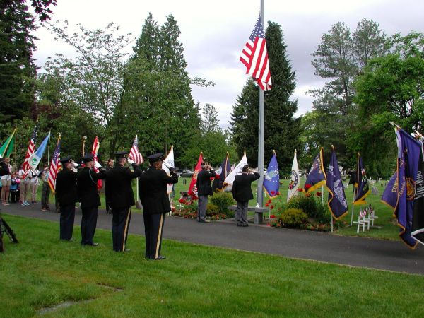 The color guard salutes as the flag is raised.