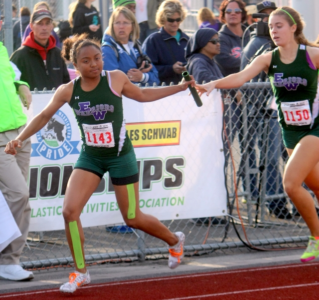 E-W's Djenne Dickens (left) takes the handoff from Savannah VanCitters during a preliminary heat of the 1,600-meter relay. The Warriors finished 11th overall in the event.
