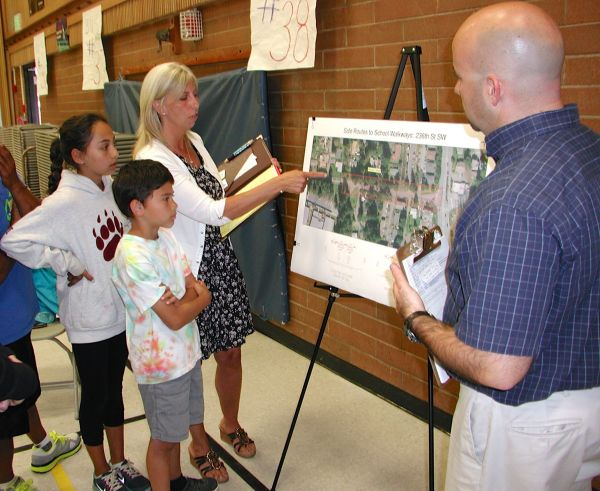 Madrona parent Keogh Singkeo, with children Sarah and Ryan, points out a problem area to City Capital Projects Manager Ryan Hague.