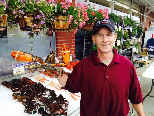 Christopher Russ of the Edmonds IGA market shows off a 2-pound Maine lobster. The store is selling lobsters, cooked or uncooked, Friday and Saturday in front of its downtown, 5th Avenue store. Most are a pound to a pound and a half in size. (Photo by Chuck Woodbury)