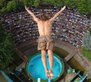courage man jumping into pool from way above