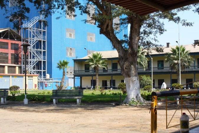 Blick auf die Casa Hacienda von Casa Grande durch eine Öffnung in der Fabrikmauer