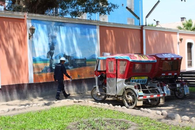 Zockerrohrarbeiter vor der Fabrikmauer, die mit Motiven aus der Blütezeit dekoriert ist.