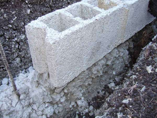 """Detail of how a badly out of level footer is """"corrected"""".  The footer is about 6"""" below the block."""