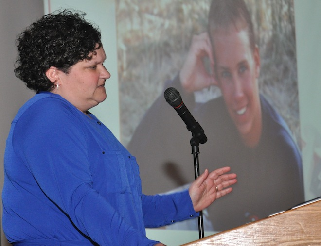 Patricia Hanson, Racine County's deputy district attorney speaks about the downfall and death by overdose of her heroin-addicted cousin Nick (whose image is projected in the background) during an emotional presentation May 6 in Burlington. Even with her access to criminal justice and rehabilitation resources, Hanson was unable to break heroin's grip on Nick. (Photo by Ed Nadolski)