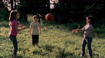 Crianças jogando bola na floresta