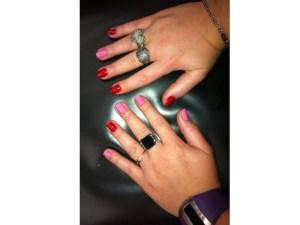 Duas mãos com as unhas pintadas de vermelho e rosa no estilo filha únia invertido.