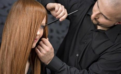 Foto de uma mulher sendo penteada por cabelereiro
