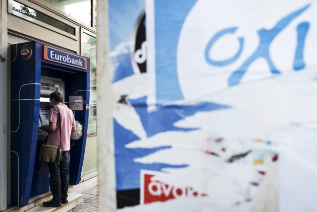A man withdraws money from an ATM in downtown Athens on July 4, 2015. (Andreas Solaro/AFP/Getty Images)