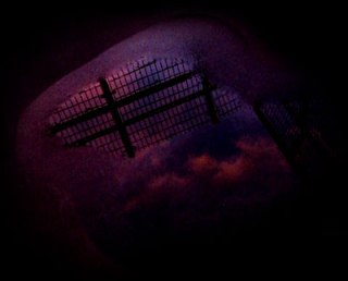 水溜りに映るフェンスと空の写真素材