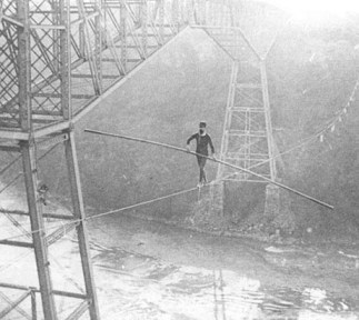 An old picture shows a man on a tight rope crossing Niagara River.