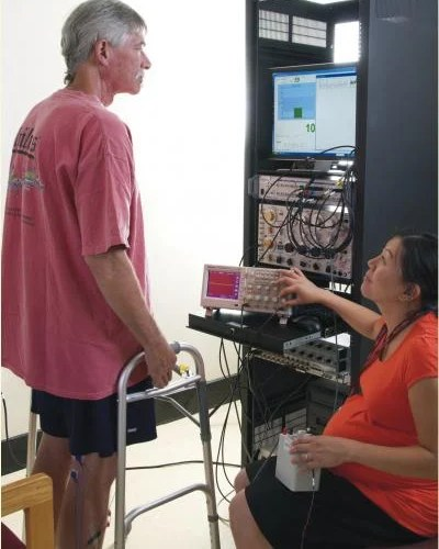 A man is standing with the help of a walker in front of a tower of electronics as a woman sits nearby.