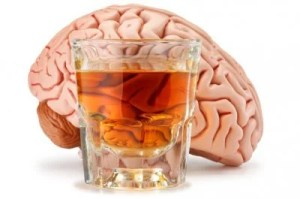 This image shows a brain with a glass of an alcoholic drink in front of it.