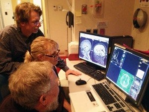 The image shows the researcher reviewing brain scans associated with the research.