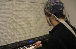 The image shows a person playing a piano wearing an eeg.