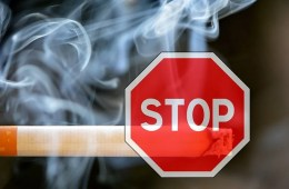 Image shows a cigarette and a stop sign.