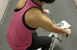 Image shows a woman on an exercise bike.