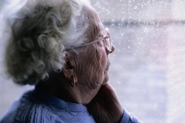 Image shows an old lady looking out of a window.