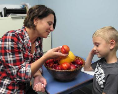 Image shows a mom and son eating a peach.