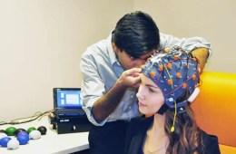 Image shows a girl in an EEG cap.