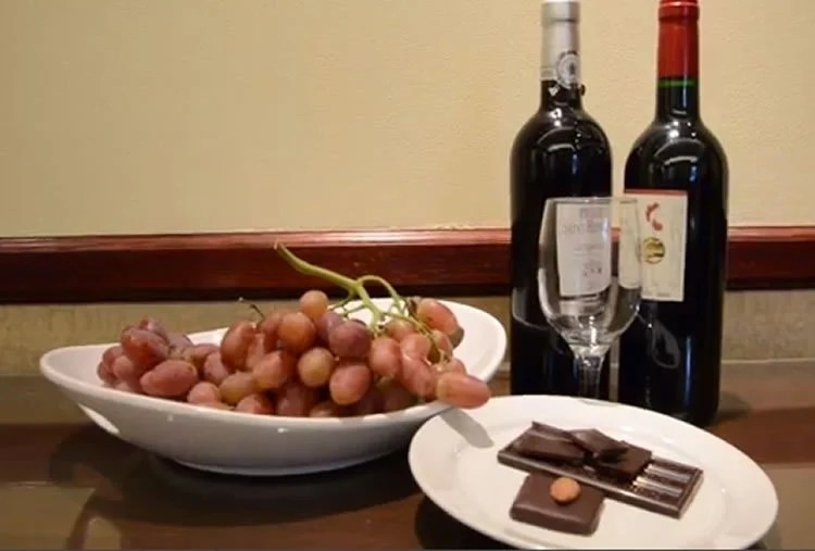 Image shows a bar of chocolate and a bottle of wine.