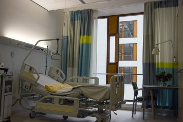 Image shows an empty hospital bed.