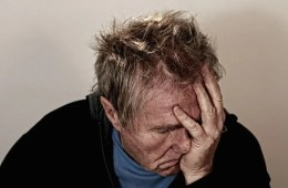 Image shows a depressed looking old man.