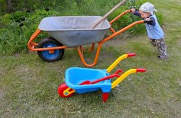 Image shows a young child pushing a wheelbarrow.