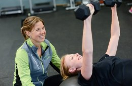 Image shows a lady lifting weights.