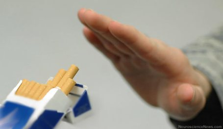 A hand is shown waving off a pack of cigarrettes.