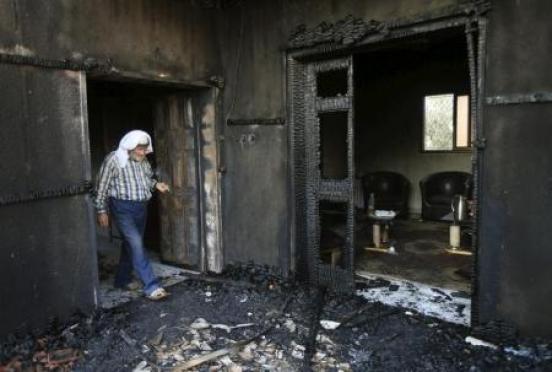 فلسطيني في منزل دمر بسبب هجوم شنه متطرفون يهود على منزلين في كفر دوما بنابلس في الضفة الغربية يوم 31 يوليو تموز 2015 - رويترز