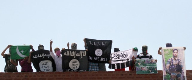 SRINAGAR, INDIA - AUGUST 28: Masked Kashmiri youth hold ISIS, Lashkar-e-Taiba flags and posters of Pakistan founder Mohammad Ali Jinnah and former ISI Chief Hamid and local militant commander of Hizbul Mujahideen Burhan during a protest outside Jamia Masjid in downtown Srinagar, on August 28, 2015 in Srinagar, India. The police had to fire tear gas shells to disperse the stone-pelting mob and restore law and order. (Photo by Abid Bhat/Hindustan Times via Getty Images)