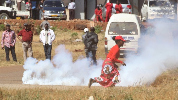 A woman ran past teargas as opposition party supporters clashed with police in Harare.