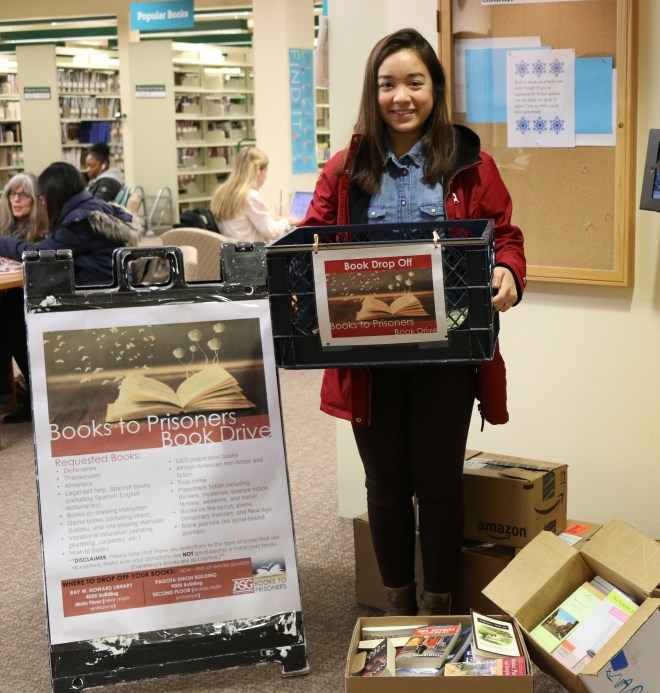 Associated Student Government Social Justice Officer Emily Stensland with some of the many books that have already been donated to the Books to Prisoners book drive.