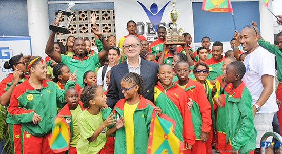 Chairman of the Board for Sagicor, Stephen McNamara (centre) and President  of the St Lucia Amateur Swimming Association, Lance Arnold (extreme right)  with the jubilant Grenada National Swim Team that won the 2013 OECS Swimming Championships.