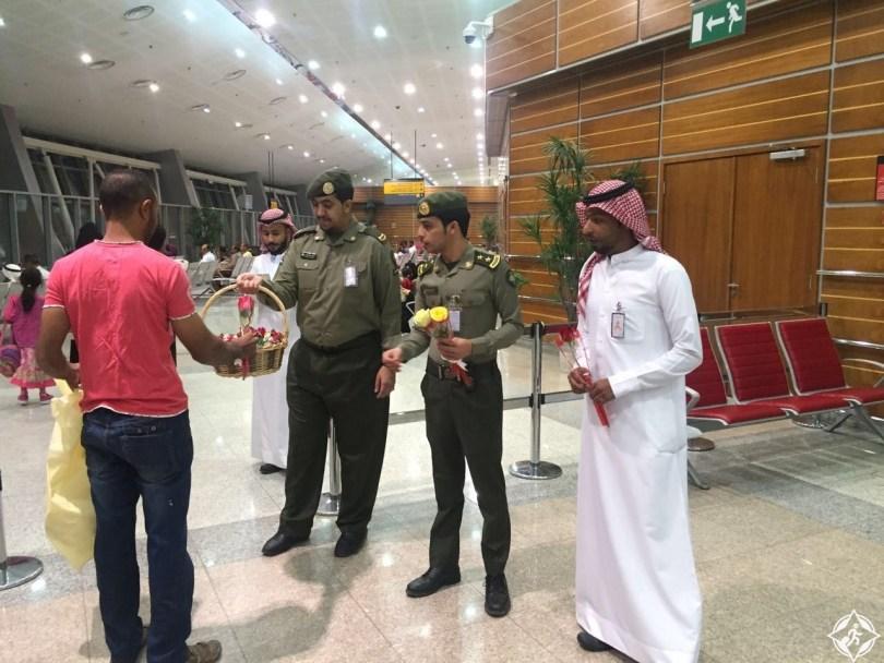 جوازات مطار الأمير سلطان بن عبدالعزيز يوزع الحلوى و الورود على المسافرين
